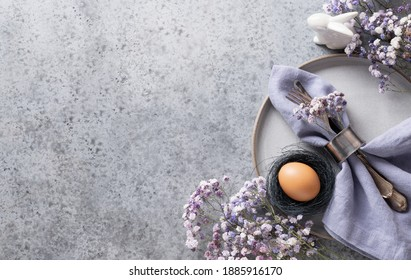 Easter table setting with violet decor on grey table. Elegance dinner. Top view. Space for text.
