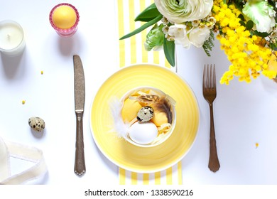 Easter table settings with painted eggs and spring flowers. Top view. Holiday flat lay