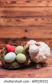 easter toy sheep near eggs basket with copyspace above on old wood background