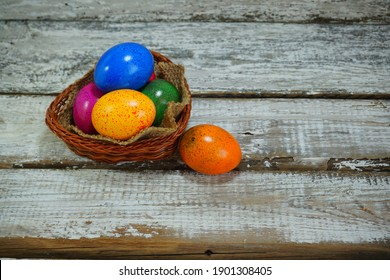 Easter tradition - Easter colorful eggs in a basket on a gray background - Easter composition. - Selective focus