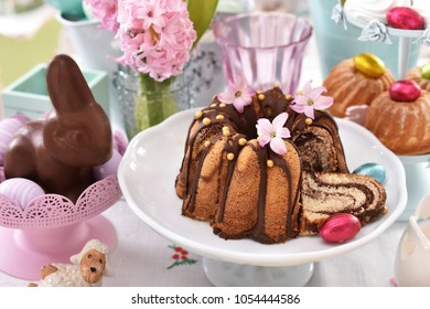 easter traditional marble ring cake with flower decoration and chocolate bunny  on festive table