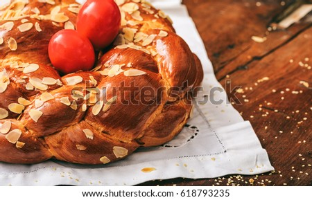 Easter traditional sweet bread, greek tsoureki and red eggs on a table