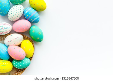 Easter traditions. Colorful Easter eggs in basket on white background top view copy space border
