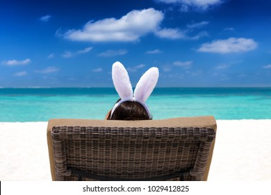 Easter travel concept: Woman with bunny ears on a tropical beach