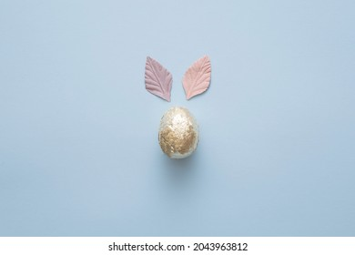 Easter unique gold egg in aluminium foil on pink background. Pink and purple leaves ears.Easter minimal concept.