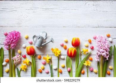 Easter wooden background with flowers, eggs and candy