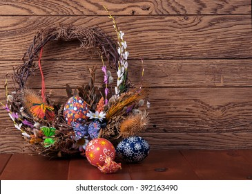Easter wreath with easter eggs, decorative butterflies, flowers and blooming willow on the wooden background. easter decorations. Happy Easter