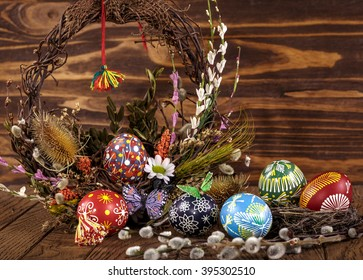 Easter wreath with easter eggs, decorative butterfly, flowers and blooming willow on the wooden background. easter decoration. happy easter