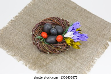Easter wreath or nest of willow branches with origami crocuses on a white background. Easter table decoration