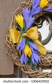 Easter wreath of willow branches with origami crocuses on a white background. Easter door decoration