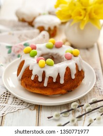 Easter yeast cake (Babka) covered with icing and decorated with marzipan eggs on a white plate on a wooden table. Traditional Easter cake in Poland