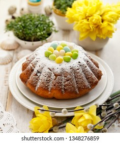 Easter yeast cake sprinkled with powdered sugar, decorated with marzipan eggs. Traditional Easter cake