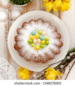 Easter yeast cake sprinkled with powdered sugar, decorated with marzipan eggs, top view. Traditional Easter cake