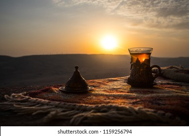 Eastern black tea in glass on a eastern carpet. Eastern tea concept. Armudu traditional cup. Sunset background. Selective focus