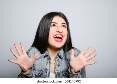Eastern brunette girl embarrassed, hipster denim dress, isolated studio portrait emotions