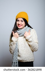 Eastern brunette girl showing thumbs up, everything is OK, hipster in winter clothes, isolated studio portrait emotions