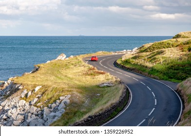 The eastern coast of Northern Ireland and Antrim Coastal Road, a.k.a. Causeway Coastal Route with a red car sunset light