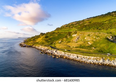 The eastern coast of Northern Ireland and Antrim Coast Road, a.k.a. Giant's Causeway Coastal Route with cars. Aerial view at sunrise.
