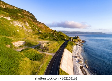 The eastern coast of Northern Ireland and Antrim Coast Road, a.k.a. Giant's Causeway Coastal Route with concrete revetments. Aerial view at sunrise.
