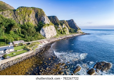 The eastern coast of Northern Ireland with cliffs and Antrim Coastal Road, a.k.a. Causeway Coastal Route. Aerial view at sunrise
