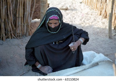 EASTERN DESERT, EGYPT - NOVEMBER 22 : Bedouin woman prepares food in the village on November 22, 1998 in Eastern Desert, Egypt. Bedouins live in harsh conditions in the desert.