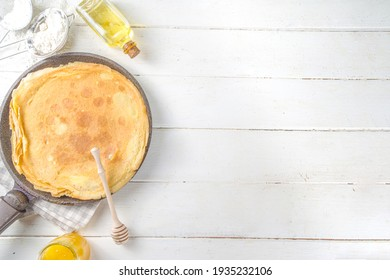 Eastern European traditional Maslenitsa holiday. Cooking crepe pancakes, with ingredients, honey and fresh berries