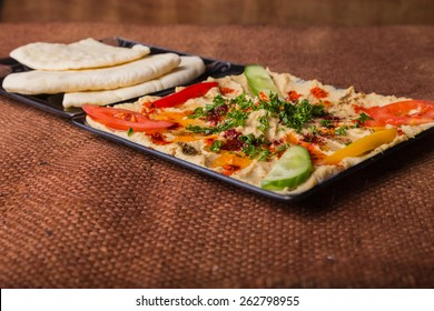 Eastern food. Snack. Hummus. Hummus with meat and greens and bread. Arab food.