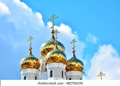 Eastern orthodox crosses on gold domes (cupolas) againts blue sky with clouds - Church on Blood in Honour of All Saints, Yekaterinburg, Russia