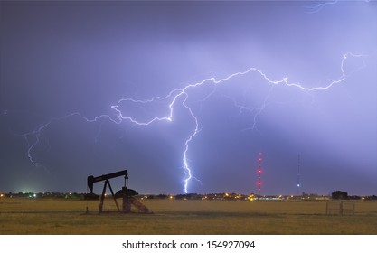 Eastern plains of the Rocky Mountain front range Weld County, Colorado, view of a pumpjack with a lightning thunderstorm strike near by.