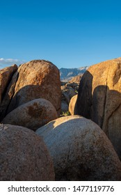 Eastern Sierra Nevada mountain range visible thru space between boulders Alabama Hills, Lone Pine, California