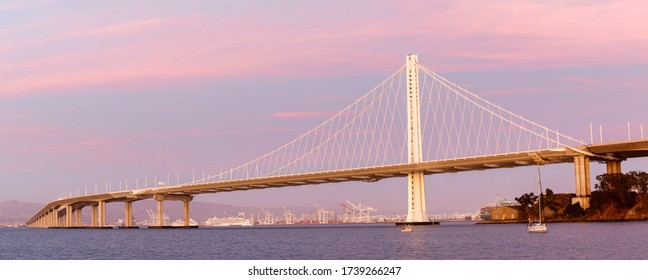 Eastern span of San-Francisco-Oakland Bay Bridge panoramic view at Twilight. Shot from Treasure Island, San Francisco, California, USA.
