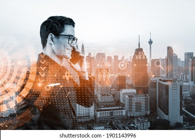 Eastern successful businessman trying to find new ideas using smartphone as a modern tool to solve problems at research and development department. Fintech hologram icons over Kuala Lumpur.