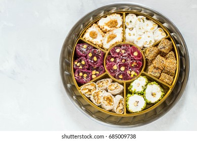 Eastern sweets. Assorted traditional Turkish delight (Rahat lokum) on gray stone background. Turkish delight with different nuts, coconut shavings and powdered sugar. Top view