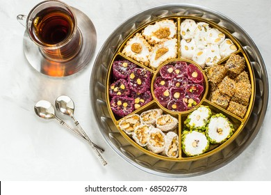 Eastern sweets. Assorted traditional Turkish delight (Rahat lokum) on gray stone background. Turkish delight with different nuts and coconut shavings, tea in glass (armud) and spoons. Top view
