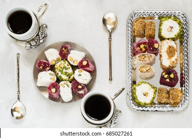 Eastern sweets. Assorted traditional Turkish delight (Rahat lokum) on gray stone background. Turkish delight with different nuts and coconut shavings, coffee in cups and spoons. Top view