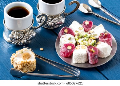 Eastern sweets. Assorted traditional Turkish delight (Rahat lokum) on blue wooden background. Turkish delight with different nuts and coconut shavings, coffee in cups, spoons and tongs for sweets