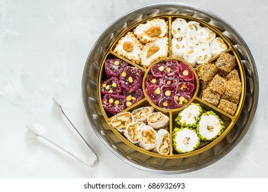 Eastern sweets. Assorted traditional Turkish delight (Rahat lokum) on gray stone background. Turkish delight with different nuts, coconut shavings, powdered sugar and tongs for sweets. Top view