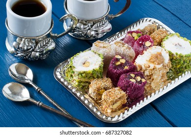 Eastern sweets. Assorted traditional Turkish delight (Rahat lokum) on blue wooden background. Turkish delight with different nuts and coconut shavings, coffee in cups and spoons
