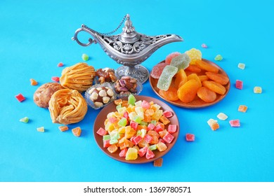 eastern sweets with baklava, marmalade, dried apricots, candied fruits assortment and metal vase on blue background