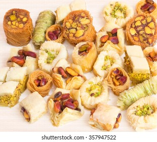 Eastern sweets variety baklava, mamoul, barazek, sharhat and ush on a pink straw background