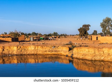 Eastern township of Ouagadougou on a sunny day with a hole filled with rainwater in the foreground, Burkina Faso.