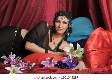 eastern woman in black clothes lies on pillows, eastern harem