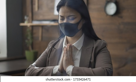 Eastern woman praying in silence while sitting at office desk. Beautiful woman in mask closed her eyes and clasped hands in prayer to God. Meditation and prayer concept. Pandemic concept.