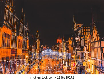 Eastgate Street Chester, UK at night with Christmas lights hanging from the impressive Tudor black and white buildings