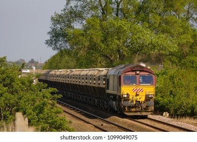 EASTREA, CAMBRIDGESHIRE, UK - APRIL 27, 2011: Euro Cargo Rail Class 66/0 No. 66029 hauls a train of loaded sand hoppers through a sun-drenched Eastrea, with the 6E88 Middleton Towers to Goole working.