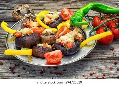 Easy appetizer of mushrooms stuffed with cheese,garlic and tomatoes.Rustic kitchen.Photo tinted.