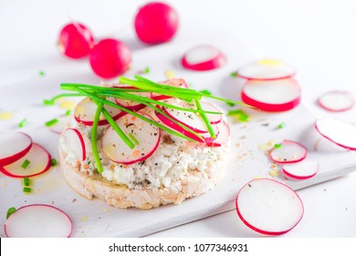 Easy breakfast concept with crisp bread, radish slices, scallion, cottage cheese and pepper. Healthy snack in high key with copy space.