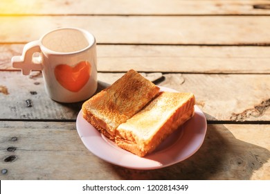 Easy breakfast, a cup of coffee  and toast on wooden table.