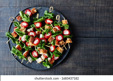 Easy chicken kebabs of peppers stuffed with cream cheese, roasted chicken breasts and spinach on skewers on a black plate on a dark wooden background, horizontal view, close-up, top view