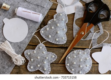 Easy Christmas crafts to make at home. Gray felt fir tree, ball and star decorated with white beads, scissors, thread, needle, paper patterns, thimble, cord on a vintage wooden table. Top view